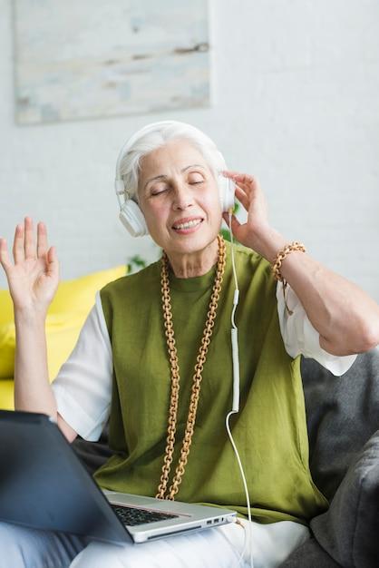 Porträt der hörenden musik der älteren frau auf kopfhörer Kostenlose Fotos