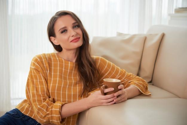 Porträt der hübschen frau sitzend auf dem boden am sofa, das warmen tee und das lächeln trinkt Kostenlose Fotos