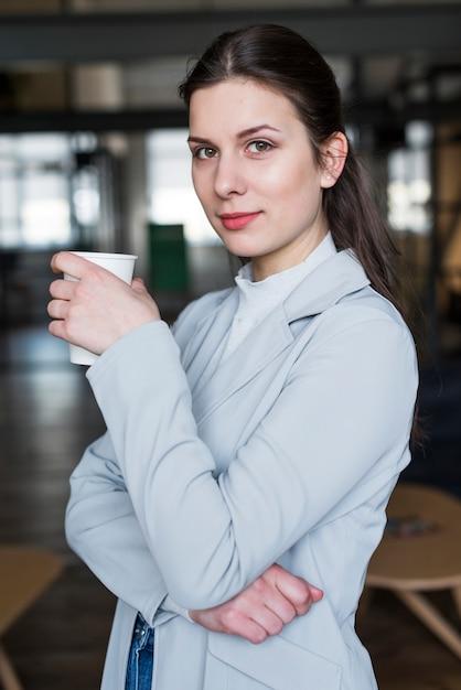 Porträt der hübschen geschäftsfrau kaffeetasse halten Kostenlose Fotos