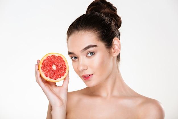 Porträt der hübschen halbnackten frau mit dem natürlichen make-up, das rote orange nahe ihrem gesicht und schauen hält Kostenlose Fotos