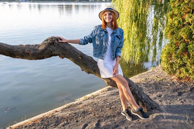 Porträt der hübschen jungen frau im kurzen rock der freizeitkleidung und im hut im herbstpark. Premium Fotos