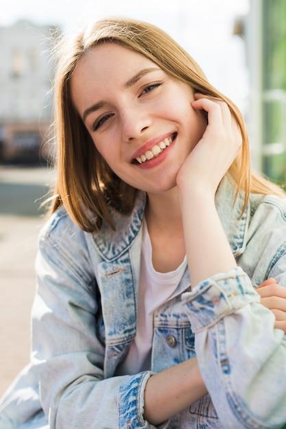 Porträt der hübschen lächelnden jungen frau, die kamera betrachtet Kostenlose Fotos