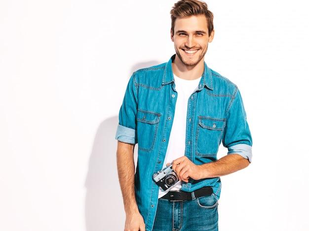 Porträt der hübschen lächelnden tragenden sommerjeans des mannes kleidet. vorbildlicher mann, der foto auf alter weinlesefotokamera macht. Kostenlose Fotos