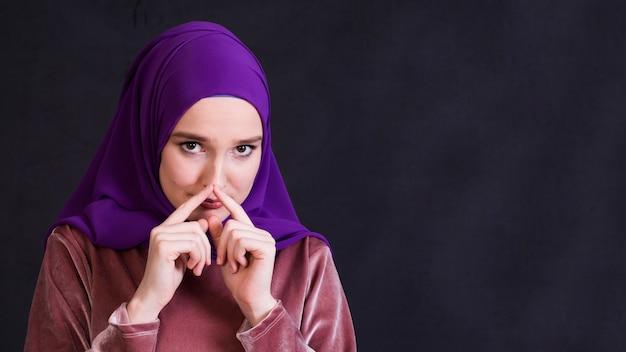 Porträt der islamischen frau tragendes hijab, das kamera betrachtet Kostenlose Fotos