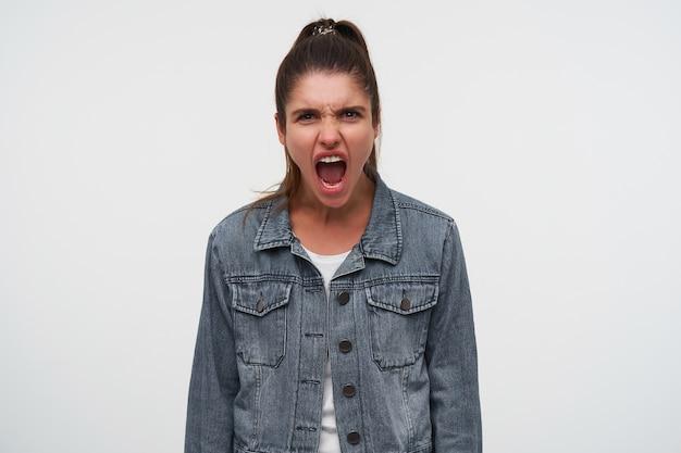 Porträt der jungen aggressiven brünetten dame trägt in weißem t-shirt und jeansjacken, schreit und sieht wütend aus, steht über weißem hintergrund. Kostenlose Fotos