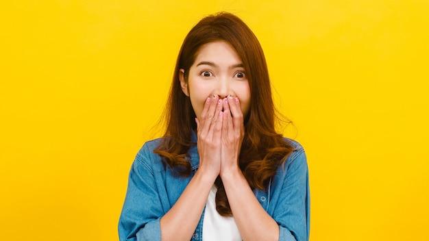 Porträt der jungen asiatischen dame mit positivem ausdruck, freudiger überraschung funky, gekleidet in lässiger kleidung und blick auf die kamera über gelber wand. glückliche entzückende frohe frau freut sich über erfolg. Kostenlose Fotos