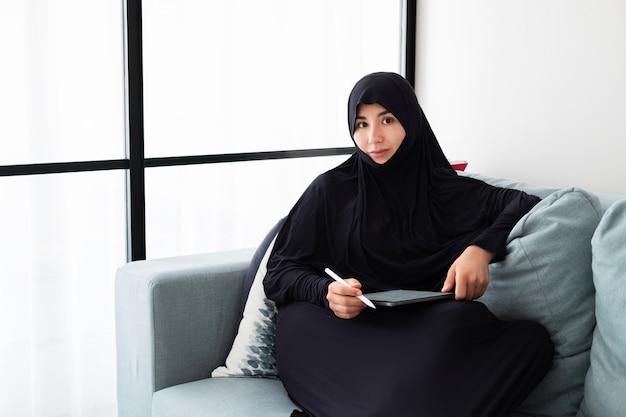 Porträt der jungen asiatischen frau, die hijab trägt und zu hause mit tablette arbeitet Premium Fotos