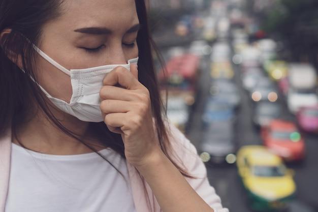 Porträt der jungen asiatischen frau, die medizinische gesichtsmaske in der stadtstraße trägt. Premium Fotos
