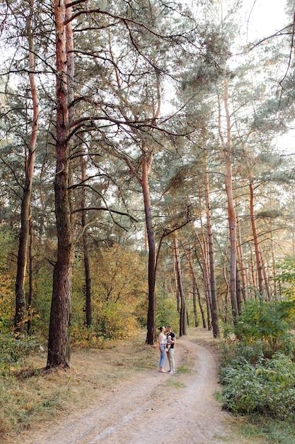 Porträt der jungen attraktiven familie mit dem kleinen kleinen sohn, der im schönen herbstkiefernwald am sonnigen tag aufwirft. hübscher mann und seine hübsche brünette frau Kostenlose Fotos