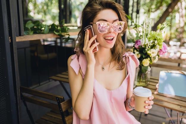 Porträt der jungen attraktiven frau, die im café sitzt, sommermode-outfit, rosa baumwollkleid, sonnenbrille, lächelnd, kaffee trinkend, stilvolle accessoires, trendige kleidung, am telefon sprechend Kostenlose Fotos