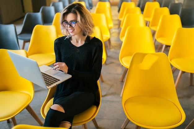 Porträt der jungen attraktiven frau, die im hörsaal sitzt, der auf laptop trägt, der brille trägt, student, der im klassenzimmer mit vielen gelben stühlen lernt Kostenlose Fotos