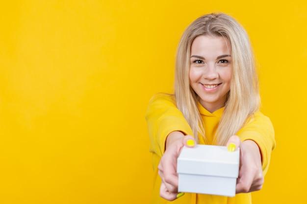 Porträt der jungen attraktiven glücklichen kaukasischen blonden frau im gelben sportanzug, geben eine weiße geschenkbox zur kamera, Premium Fotos