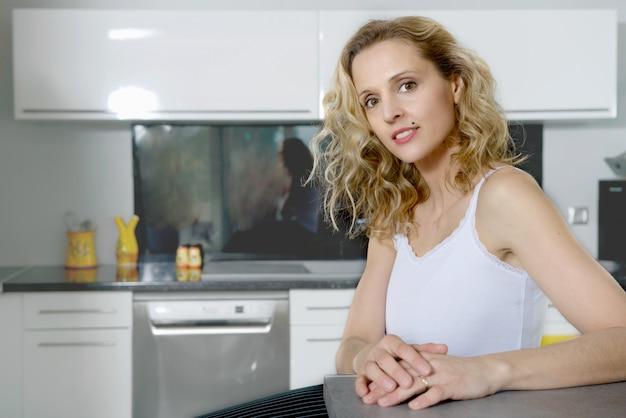 Porträt der jungen blonden frau in der küche Premium Fotos