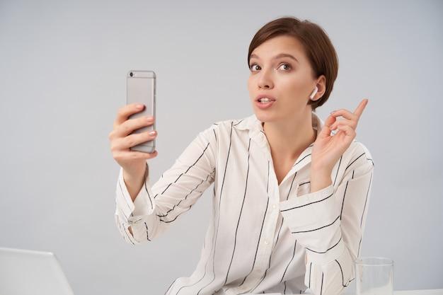 Porträt der jungen braunäugigen kurzhaarigen brünetten geschäftsfrau, die videoanruf mit ihrem smartphone macht, während auf weiß im gestreiften formellen hemd sitzt Kostenlose Fotos