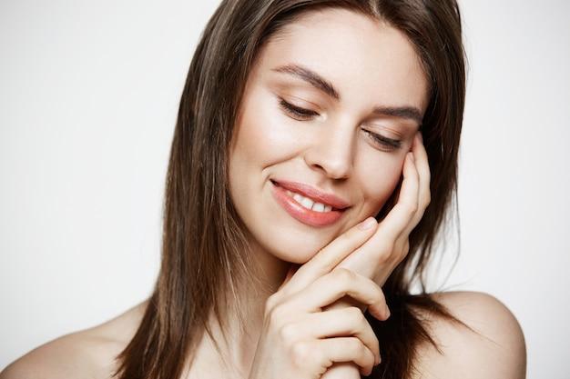Porträt der jungen brünetten schönen frau, die berührendes gesicht lächelt. spa schönheit gesund und kosmetologie konzept. Kostenlose Fotos