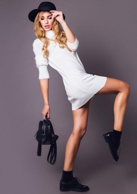 Porträt der jungen eleganten blonden frau im hut und im stilvollen weißen winterpullover Kostenlose Fotos