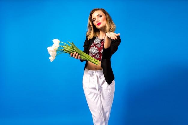 Porträt der jungen eleganten frau mit hellem make-up und dunklem blazer, die weiße blumen hält Kostenlose Fotos