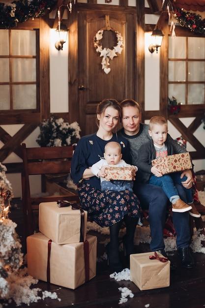 Porträt der jungen familie mit zwei kindern, die auf bank mit weihnachtsgeschenken kuscheln Premium Fotos