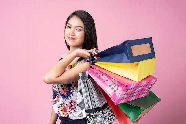 Porträt der jungen frau bunte einkaufstaschen mit lächeln tragend Premium Fotos
