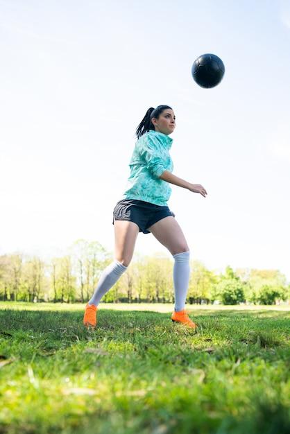 Porträt der jungen frau, die fußballfähigkeiten übt und tricks mit dem fußball macht Kostenlose Fotos