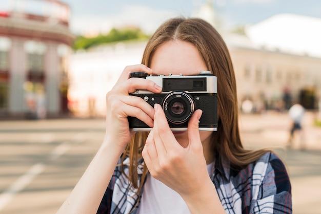 Porträt der jungen frau foto mit kamera machend Kostenlose Fotos