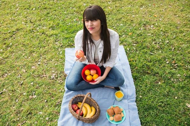 Porträt der jungen frau frische früchte im park halten Kostenlose Fotos