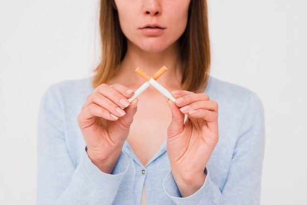 Porträt der jungen frau gekreuzte zigaretten halten Kostenlose Fotos