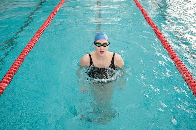 Porträt der jungen frau in der badekappe und in der schutzbrille, die aus dem wasser im pool gleiten Premium Fotos