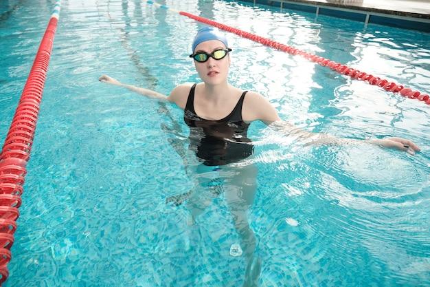 Porträt der jungen frau in der schwimmbrille und in der kappe, die im pool sich entspannen Premium Fotos
