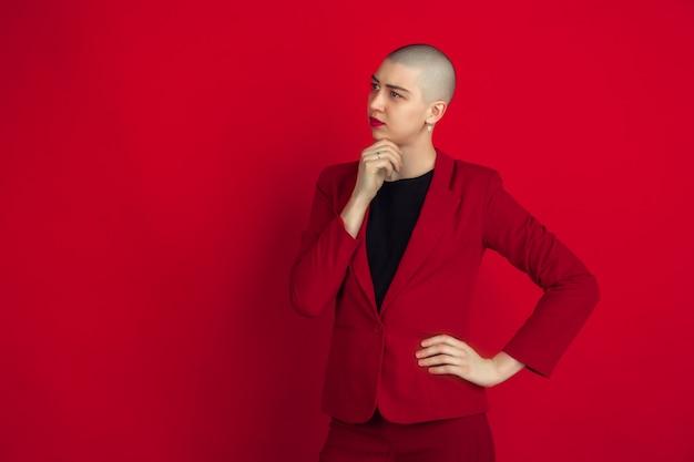 Porträt der jungen frau mit ausgeflipptem aussehen auf roter wand Kostenlose Fotos