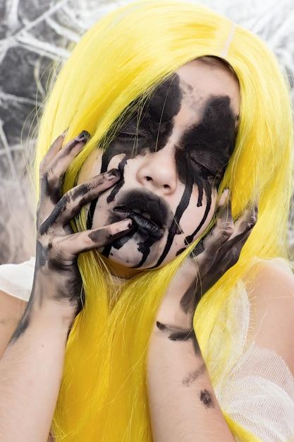 Porträt der jungen frau mit dem gelben haar mit furchtsamem halloween-make-up Premium Fotos