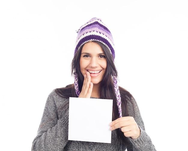 Porträt der jungen frau mit einer woolen haltenen zeichenkarte der strickjacke und des peruanischen hutes Premium Fotos