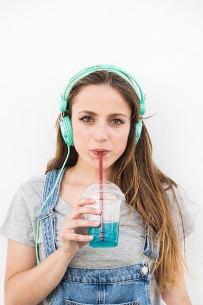 Porträt der jungen frau tragenden trinkenden saft des kopfhörers mit stroh Kostenlose Fotos