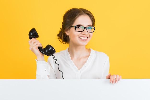 Porträt der jungen geschäftsfrau mit dem telefon, das leere anschlagtafel auf gelber wand zeigt Premium Fotos