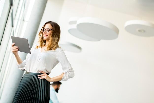 Porträt der jungen geschäftsfrau stehende wirth tablette im büro durch fenster Premium Fotos