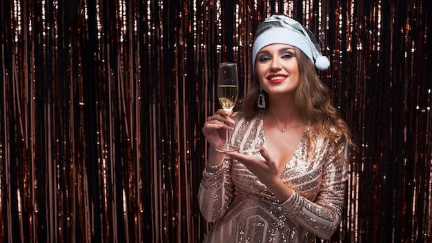 Porträt der jungen glücklichen frau in silbernem sankt-hut mit champagnerglas in den händen. Premium Fotos