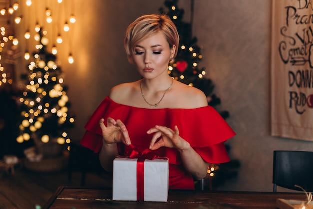 Porträt der jungen glücklichen netten frau im roten kleid mit präsentkarton des neuen jahres in den händen im weihnachten verzierte nach hause. weihnachten, glück, schönheit, geschenkkonzept Premium Fotos