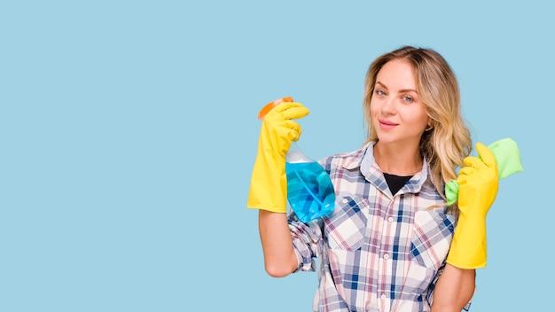 Porträt der jungen hausmeisterfrau, die reinigungsmittelsprühflasche und -serviette hält Kostenlose Fotos