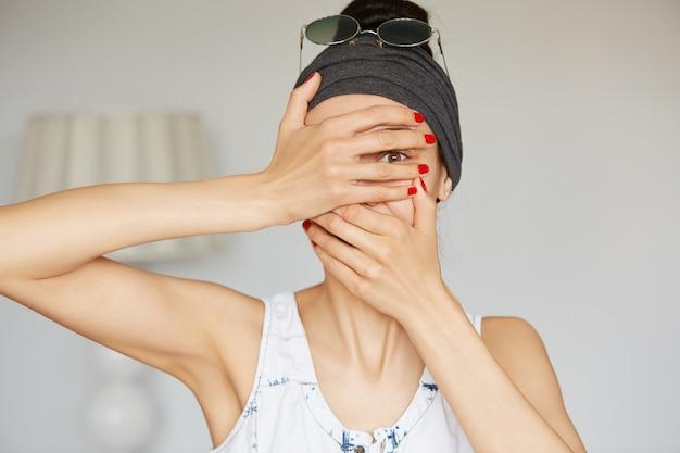 Porträt der jungen hipsterfrau, die durch ihre finger guckt Kostenlose Fotos