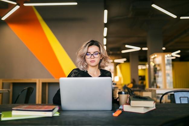 Porträt der jungen hübschen frau, die am tisch im schwarzen hemd sitzt und am laptop im mitarbeitenden büro arbeitet Kostenlose Fotos