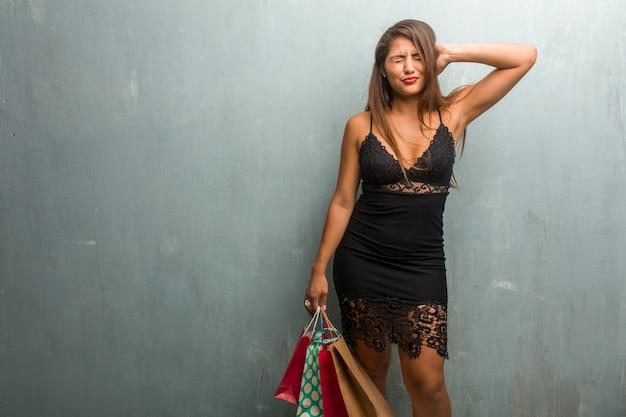 Porträt der jungen hübschen frau, die ein kleid gegen ohren einer wandbedeckung mit den händen trägt Premium Fotos