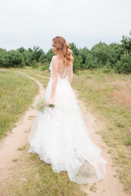 Porträt der jungen hübschen frau im weißen hochzeitskleid draußen Premium Fotos