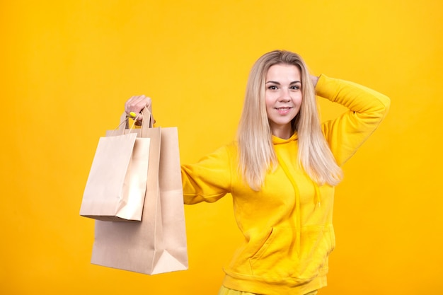 Porträt der jungen hübschen kaukasischen blonden frau mit papieröko-taschen im gelben sportanzug, lokalisiert Premium Fotos