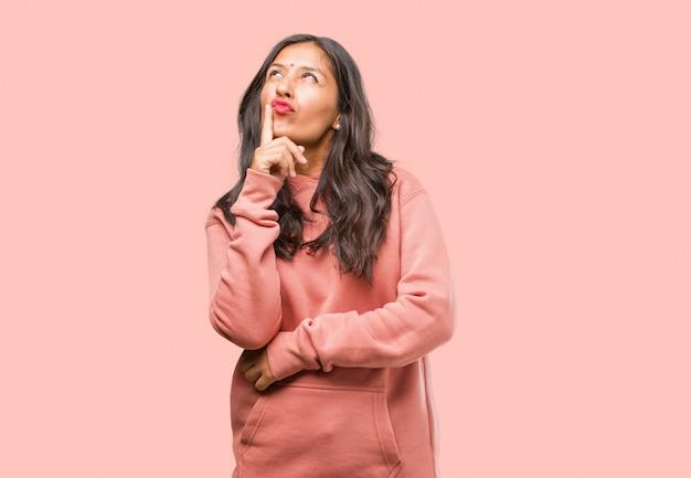 Porträt der jungen indischen frau der eignung, die oben, verwirrt über eine idee denkt und schaut, würde versuchen, eine lösung zu finden Premium Fotos