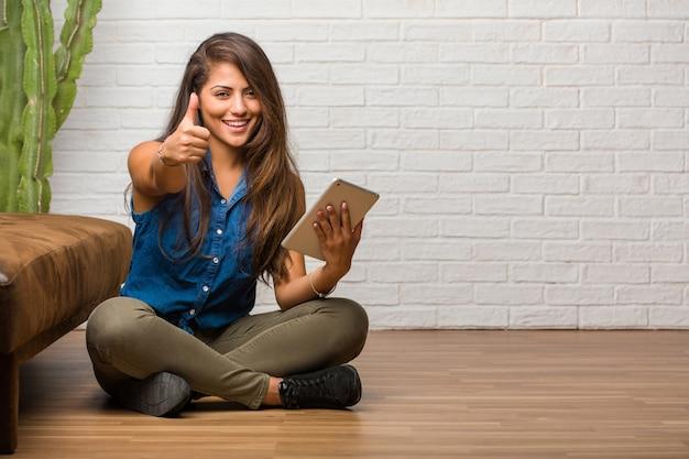Porträt der jungen lateinischen frau, die auf dem fußboden nett und aufgeregt sitzt Premium Fotos