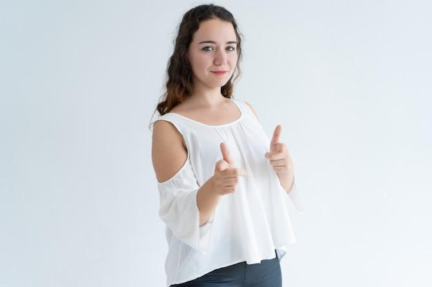 Porträt der jungen positiven frau, die auf die kamera wählt sie zeigt Kostenlose Fotos
