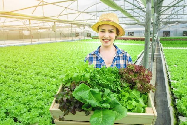Porträt der jungen schönen asiatin, die frischgemüsesalat von ihrem hölzernen korb und lächeln des hydrokulturbauernhofhandgriffs erntet Premium Fotos