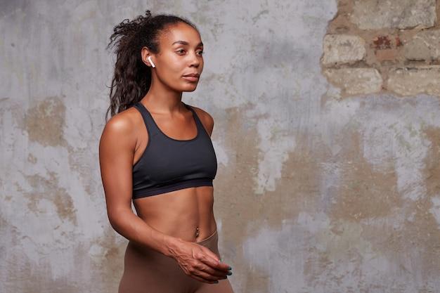Porträt der jungen schönen athletischen dunkelhäutigen lockigen sportlerin mit kopfhörern in ihren ohren, die über mauer gehen Kostenlose Fotos