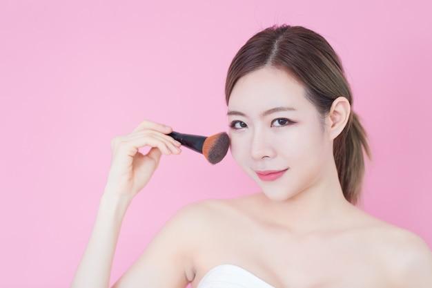 Porträt der jungen schönen kaukasischen asiatischen frau, die kosmetisches bürstenpulver aufträgt Premium Fotos