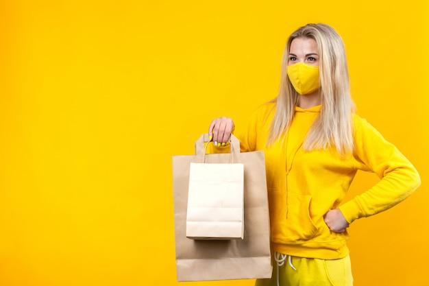 Porträt der jungen schönen kaukasischen blonden frau mit papier-öko-tasche in der gelben schutzmaske lokalisiert, Premium Fotos
